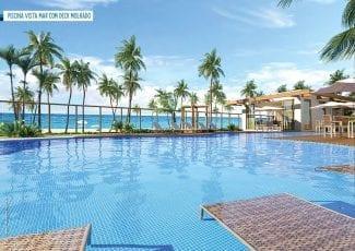 Perspectiva da piscina com vista mar e deck molhado. Casas à venda em condomínio em Itacimirim.