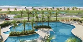 Perspectiva da piscina com vista para a praia